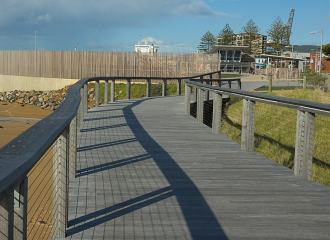 A beachside boardwalk path, leading to some buildings, the path has handrails on both sides
