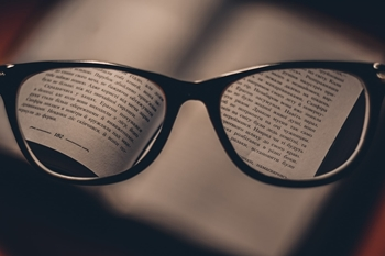 Black framed eye glasses resting on a book, with the text magnified.jpg