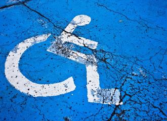 International Symbol of Access, painted white on blue background, on concrete floor surface