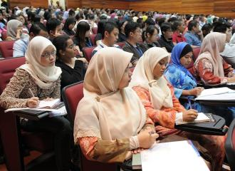 Lecture hall with students all seated looking towards the front-min