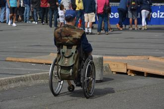 Person using a wheelchair trying to get into an event space and over a portable ramp