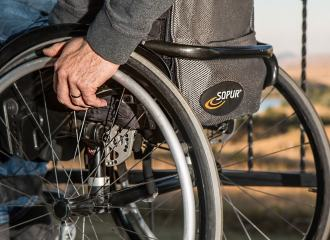 View of the rear of a wheelchair with a man seated in it