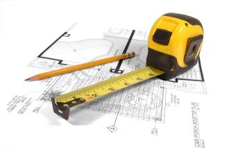 Tape measure and pencil laying on an architectural floor plan