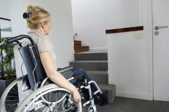 A lady in a wheelchair stares at the bottom of some stairs