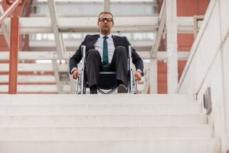 A man in a wheelchair stares down from the top of the stairs