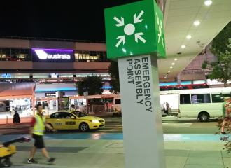 Emergency Assembly Point sign on a column outside an airport terminal
