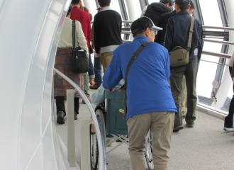 Tourist pushing their partner in a wheelchair around the observation deck