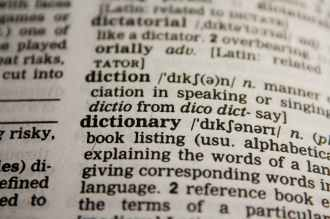 Close up photo of a dictionary page open to the word DICTIONARY