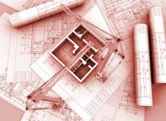 Architectural plans laid out on a table, with a model model shown in 3 dimensions, with wall only, and two model cranes leaning over the building